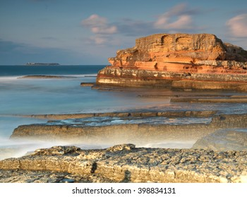 Long exposure shot on amazing pink rocks and sea