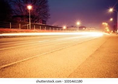 """Long exposure shot in pastel colours of a city road with vehicles light trails and public lighting on the sides, in the city of """"Fribourg"""" in Switzerland"""