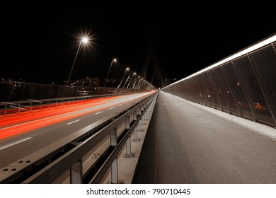 """Long exposure shot of the """"Poya"""" bridge in the city of """"Fribourg"""" in Switzerland, with red vehicles light trails on the left"""