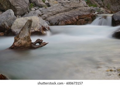Long exposure shot of the river in Valbona, Tropoja, Albania. Grey rocks and a picturesque log in the middle of the water