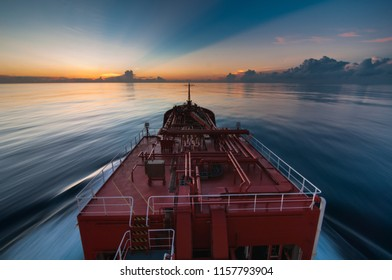 Long exposure shot with a ship sailing towards a beautiful sunest with rays of light and clouds
