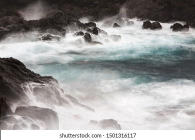 Long exposure shot of tall splashing waves hitting the rocks with tiny waterfalls running down at Playa de Nogales in La Palma, Spain.