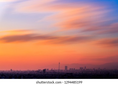long exposure shot of Tehran skyline at the sunset with colorful sky and smooth clouds and milad tower frame at the middle.