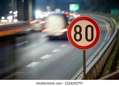 Long exposure shot of traffic sign showing 80 km/h speed limit on a highway full of cars in motion blur during the night