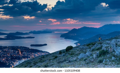 Long exposure shot of a young couple overviewing the city of Dubrovnik, Croatia from the top of the hill just after sunrise