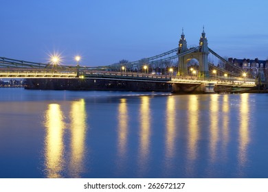 Long exposure side shot of Hammersmith Bridge, in West London, over the river Thames at dusk.