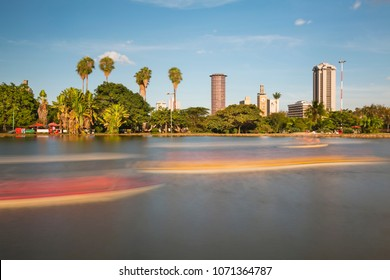 Long exposure of the skyline of Nairobi, Kenya with the beautiful lake in Uhuru Park in the foreground and some blurred boats.