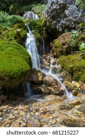 Long exposure of a small waterfall coming down through rocks and moss