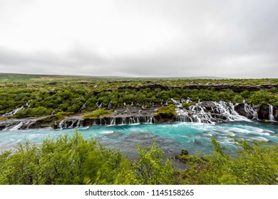 Long exposure smooth colorful blue aqua turquoise water waterfall cascades Hraunfossar Lava Falls in Iceland, landscape view