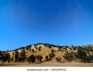 Long exposure of star trails over a moonlit hill in Northern California