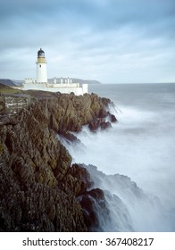 Long Exposure of a Stormy Sea with Lighthouse on top of Rocky Cliffs. Location, Douglas,  Isle of Man, United Kingdom