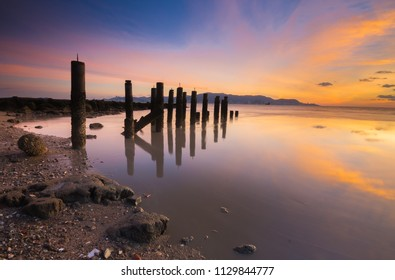 Long Exposure Sunset Seascape with old jetty formation in foreground, Robina Beach, Pulau Pinang, Malaysia. Soft Focus, Motion Blur Due to Long Exposure Shot.