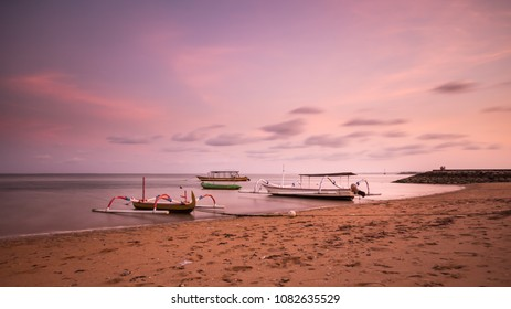 Long exposure of sunset taken on Sanur beach with boats in the water