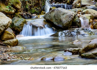 Long Exposure to take running water in River with Green Moss Stone In Forest