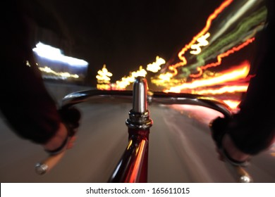 Long exposure taken from a camera fixed  on a fixed gear bicycle at night. In the forehand a close up of the handlebar.