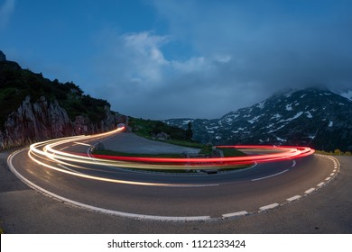 Long exposure traffic on dark mountain road at Sustenpass, bernese oberland, wide angle view of glowing lights of exposure traffic on paved winding roadway in mountains under dark clouds