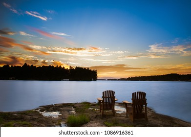 Long exposure of two Muskoka chairs sitting on a rock formation facing a calm lake at dusk in cottage country.