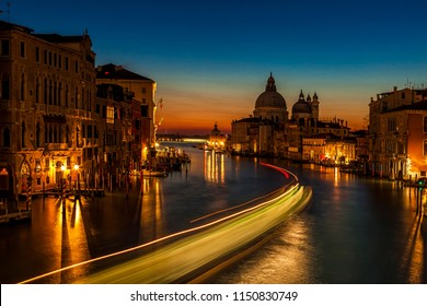 Long exposure of a vaporetto traveling up the Grand Canal towards the Santa Maria della Salute church as seen from the Accademia Bridge in Venice, Italy