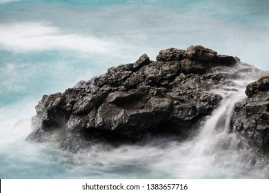 Long exposure of volcanic lava rocks in the south of La Palma, Spain with little waterfalls and turquoise water.