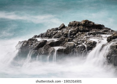 Long exposure of volcanic lava rocks in the south of La Palma, Spain with little waterfalls from the surf and turquoise water.
