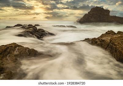 Long exposure water, beautiful seascape, ocean views, rocky coastline, sunlight, on the horizon. Composition of nature. Sunset scenery background. Cloudy sky. California coast. - Shutterstock ID 1928384720