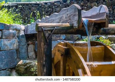 Long exposure of water emptying from trough onto waterwheel. Small amount of motion blur on wheel due to long exposure for effect.