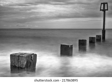 Long exposure of water moving along wooden groynes