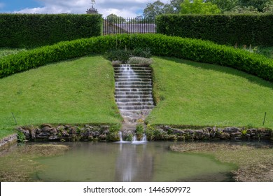 Long exposure of a waterfall flowing down stairs in an ornamental garden