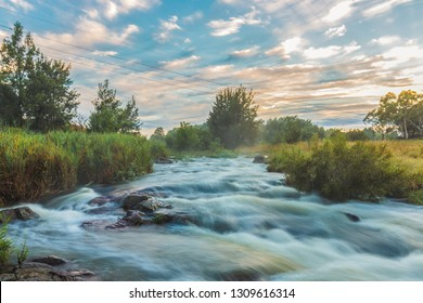 Long exposure of the waters flowing down Ginninderra Creek on a misty early morning in Umbagong District Park, Latham, ACT, Australia, showing telegraph wires extending across the creek