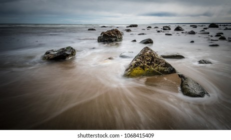 A long exposure of waves with seaweed and barnacles on rocks along the Atlantic ocean coast