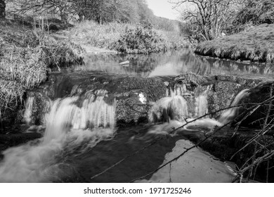 Long exposure of the Weir Water river  flowing through the valley at Robbers Bridge in Exmoor National Park - Shutterstock ID 1971725246