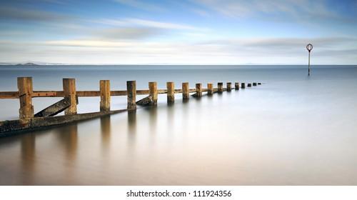 Long exposure of wooden groynes leading in to the north sea at Portobello, Edinburgh