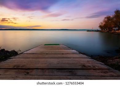 A long exposure. a wooden pier or a boardwalk goes into a lake, the water is soft and in the sky are small soft clouds that are lit up pink by the sunset. Balaton