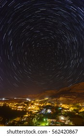 Long exposures reveal stars rotating around Polaris, the pole star. The small town is Metajna on Pag island, Croatia. HDR photo.