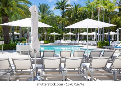 Long extension pool at Miami Beach, Florida, USA. Vacation resort in a summer sunny day. Touristic attraction in southern Florida, USA. Sun umbrellas and resting chairs around a great swimming pool.