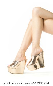 Long female legs in golden high heels mules with wedge sole