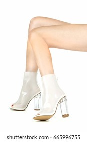 Long female legs in high heels ankle boots in shiny transparent white colour.