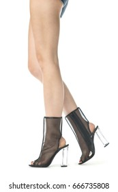 Long female legs in high heels ankle boots in transparent black mesh and clear plastic heels.
