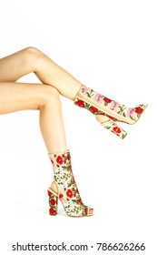 Long female legs in high heels summer boots in transparent mesh with colorful flower design.