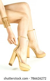 Long female legs in high heels summer boots in transparent nude/beige mesh fabric.