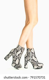 Long female legs in high heels boots in animal print/snake print design. 