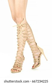 Long female legs in strappy high heels summer boots in nude color.
