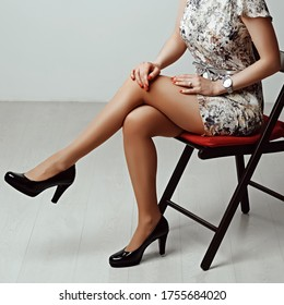 Long female legs in tan tights and high heel shoes sitting on stool