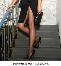 Long female legs in thin black tights, high heel shoes and black dress with deep cut descending