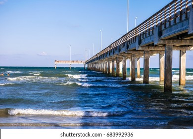 Long fishing pier extending out into the surf on Port Aransas beach along Padre island Texas national seashore a barrier island in the Gulf of Mexico near Corpus Christi , TX , USA