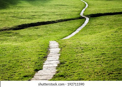 A long flagstone pathway snaking through a grassy field in the Yorkshire Dales, England, UK.