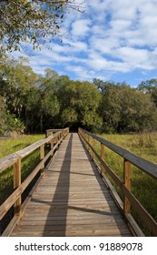 Long footbridge with interesting shadows on a nature walk trail in Myakka River State Park in Florida, with viewing alcove midway down.