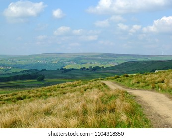 a long footpath running downhill in stoodley moor in yorkshire with fields and farms in the distance with the pennine hills on the horizon on a sunny summers day with blue sky and clouds