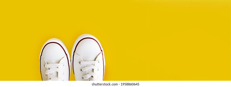 long format banner with space for text new clean sneakers with white laces on a rubber sole on a bright yellow background. selective focus