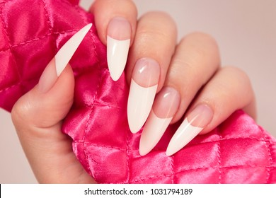 Long French manicure on the female hand close-up.Nail art.Nail extension.
